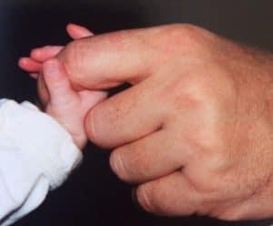 Babyhandje houdt mannenhand vast